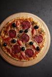 Pizza met salami, mozarellakaas, kersentomaten, zwarte olijven en orego Naar huis gemaakt voedsel Concept voor smakelijk en harte royalty-vrije stock afbeelding