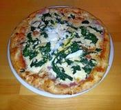 Pizza met spinazie, ham, bacon en kaas, op witte plaat, op lijst in houten decor royalty-vrije stock foto's