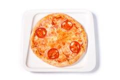 Pizza met tomaat en kaas in een witte plaat op een geïsoleerde witte achtergrond stock foto