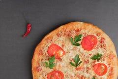Pizza met tomaat en rode Spaanse peper op grijze lijst, hoogste mening en plaats voor tekst royalty-vrije stock afbeeldingen