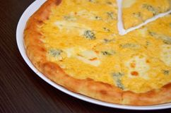 Pizza met vier kazen in een witte plaat op een donkere houten lijst, close-up royalty-vrije stock afbeeldingen