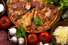 Pizza met worst en kaas en verscheidenheid van ingrediënten Stock Afbeelding