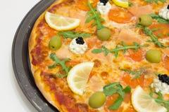 Pizza met zalm, olijven, arugula en citroen Stock Afbeelding