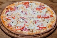 Pizza Milano on Pizza Milano creamy base, chicken fillet, mushrooms, tomatoes, mozzarella, sauce, oregano on a plate. plate. Pizza Milano creamy base, chicken Stock Photos