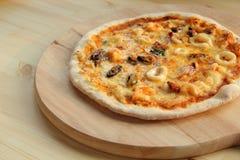 Pizza mince de fruits de mer du plat en bois Image stock