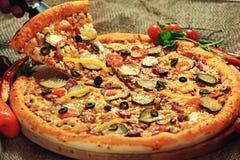 Pizza mit einem Scheibenschnitt Lizenzfreies Stockbild