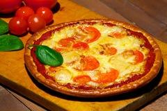 Pizza mit Gemüse auf einem alten hölzernen Brett lizenzfreies stockfoto