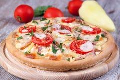 Pizza mit Huhn, Tomaten und Käse auf einem hölzernen Brett Stockfotografie