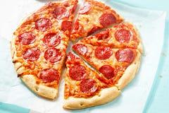 Pizza mit Käse und Pepperonis auf blauer Oberfläche stockbilder