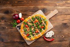 Pizza mit Kalbfleisch und getrockneten Tomaten auf einem h?lzernen Hintergrund stockfotografie