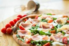 Pizza mit Kirschtomaten, Prosciutto und ruccola Stockbild