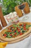 Pizza mit Kirschtomaten und Arugula Lizenzfreie Stockfotos