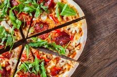 Pizza mit Mozzarellakäse, Pilzen, Pepperonis, Tomatensauce, Salami, Pfeffer, Gewürzen und frischem Arugula Italienische Pizza auf stockbild