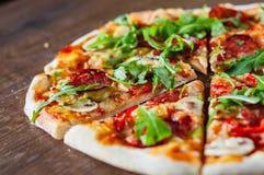 Pizza mit Mozzarellakäse, Pilzen, Pepperonis, Tomatensauce, Salami, Pfeffer, Gewürzen und frischem Arugula Italienische Pizza auf lizenzfreie stockfotos