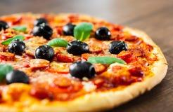 Pizza mit Mozzarellakäse, Salami, Pfeffer, Pepperonis, Tomaten, Oliven, Gewürzen und frischem Basilikum Italienische Pizza Lizenzfreie Stockbilder