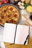 Pizza mit Notizbuch und Bestandteilen Lizenzfreie Stockbilder