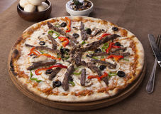 Pizza mit Rindfleischstücken und -pilz auf einem braunen Hintergrund Stockfotos