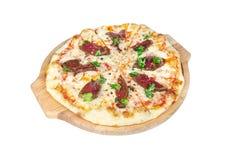 Pizza mit Roastbeef, Käse und Grüns auf einem runden Schneidebrett lokalisiert auf weißem Hintergrund stockfotos