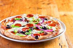 Pizza mit Salami, roter Zwiebel, Pfeffern und schwarzen Oliven stockfotografie