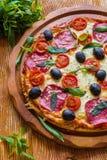 Pizza mit Salami, schwarzen Oliven und Tomaten lizenzfreies stockfoto
