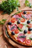 Pizza mit Salami, schwarzen Oliven und Tomaten stockfotos