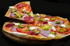 Pizza mit Schinken, Pepperonis, Essiggurken, Feta Stockfoto