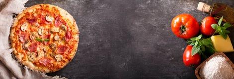 Pizza mit Schinken und Salami mit Bestandteilen für das Kochen lizenzfreie stockfotografie