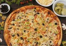Pizza mit schwarzen Oliven, Artischocken und Schinken lizenzfreies stockfoto
