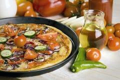 Pizza mit Soße und Teilen Stockbild