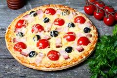 Pizza mit Speck, Oliven und Tomate lizenzfreie stockfotografie