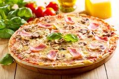 Pizza mit Speck und Pilzen Lizenzfreie Stockbilder