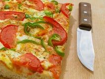 Pizza mit Tomate und grüner Paprika und Messer Stockbild