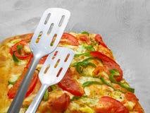 Pizza mit Tomate und grüner Paprika und Zangen Stockfoto