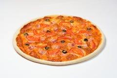 Pizza mit Tomaten, Schinken, Käse und Oliven auf einer weißen Soße auf einem weißen Hintergrund Stockbild