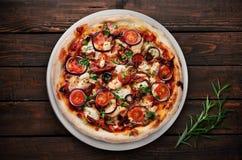 Pizza mit Tomaten, Zwiebel, Käse und Kräutern auf dunklem hölzernem Hintergrund Stockfotografie