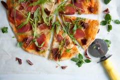 Pizza mit Tomatensauce, Prosciutto und Arugula stockfotografie