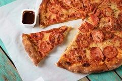 Pizza mit Würsten auf einem hölzernen Hintergrund Lizenzfreie Stockfotografie