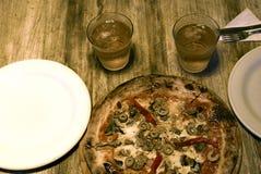 Pizza mit zwei Gläsern in einem hölzernen Hintergrund Stockfoto