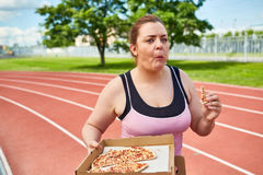 Pizza on the move. Chubby female in activewear eating pizza on the move on stadium Royalty Free Stock Photography