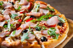 Pizza with Mozzarella cheese, ham, pepper, olive, meat, Tomato sauce, Spices and Fresh arugula. Italian pizza on wooden background stock photo