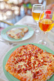 Pizza with mozzarella cheese, olive, fresh tomato and pesto sauce. Served at restaurant table with two beers Royalty Free Stock Image