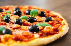 Pizza with Mozzarella cheese, salami, pepper, pepperoni, Tomatoes, olives, Spices and Fresh Basil. Italian pizza Royalty Free Stock Images