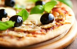 Pizza with mozzarella, mushrooms, black olives and fresh basil. Italian pizza. royalty free stock photography
