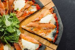 Pizza with Mozzarella, Salmon Slice and Vegetables. On a thin black dough. Cut piece. View from above. Clouse-up royalty free stock image