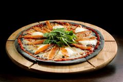 Pizza with Mozzarella, Salmon Slice and Vegetables. On a thin black dough. Side view stock photo