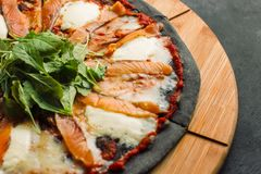 Pizza with Mozzarella, Salmon Slice and Vegetables. On a thin black dough. View from above. Clouse-up royalty free stock photography