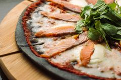 Pizza with Mozzarella, Salmon Slice and Vegetables. On a thin black dough. Clouse-up royalty free stock images