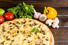 Pizza with mushrooms and cheese on a dark wooden background with stock photography