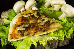 Pizza with mushrooms. Pizza piece with mushrooms dekorated with lettuce and mushrooms on a stump on a black background with reflection Stock Image