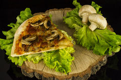 Pizza with mushrooms. Pizza piece with mushrooms dekorated with lettuce and mushrooms on a stump on a black background with reflection Royalty Free Stock Image